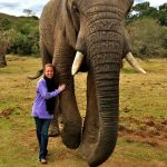 A female student standing next to an elephant
